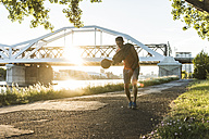 Young man dribbling basketball at the river - UUF11128