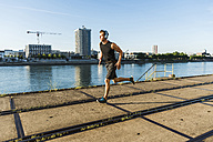 Young athlete jogging in the city at the river - UUF11137