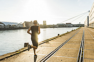 Young athlete jogging in the city at the river - UUF11140