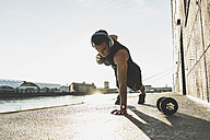Fit athlete doing push ups at the river - UUF11146