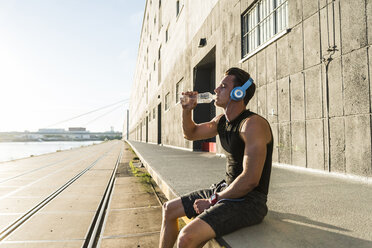 Young athlete wearing headphones, sitting on a wall - UUF11149