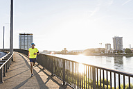 Young athlete jogging on a bridge in the city - UUF11158