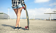 Back view of young woman with longboard in front of beach promenade, partial view - DAPF00766