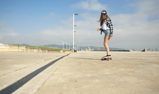 Young woman longboarding on beach promenade - DAPF00769