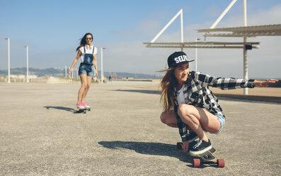Two young women longboarding on beach promenade - DAPF00775