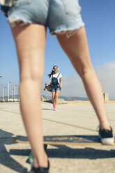 Happy young woman with longboard and headphones on beach promenade - DAPF00778