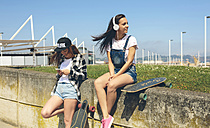 Young woman with headphones listening music while her  friend looking at smartphone - DAPF00784
