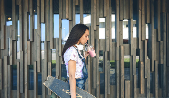 Young woman with headphones drinking strawberry smoothie - DAPF00790