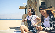 Two happy young women listening music and having fun next to the beach - DAPF00793