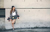 Portrait of happy young woman with longboard standing in front of concrete wall - DAPF00796