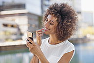 Young woman preparing for selfie, checking make up - ZEF14119