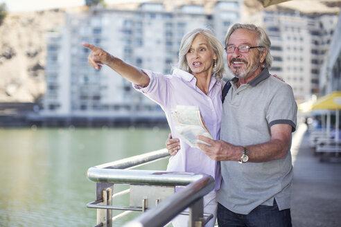 Senior couple taking a city break, holding map - ZEF14146