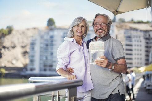 Senior couple taking a city break, holding map - ZEF14149