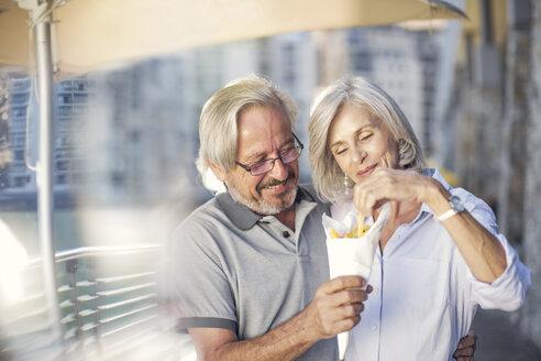 Senior couple taking a city break, eating French fries - ZEF14161