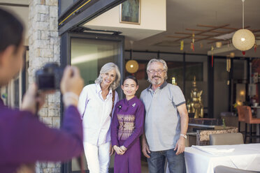 Senior couple taking pictures with Asian waitress in front of restaurant - ZEF14167