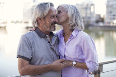 Senior couple taking a city break, kissing and embracing - ZEF14173