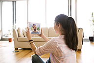 Young woman using tablet for video chat at home - HAPF01889