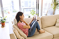 Young woman using tablet for video chat at home - HAPF01895