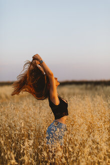 Young woman standing in grain field enjoying sunset - JPF00254
