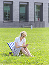 Woman with headphones sitting on a meadow looking at cell phone - LAF01849