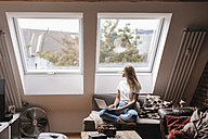 Young woman at home sitting on couch, using laptop - GUSF00101
