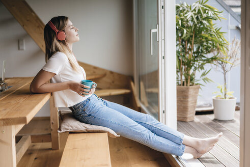 Young woman relaxing at home with a cup of tea, listening music - GUSF00128