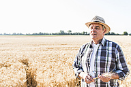 Portrait of pensive senior farmer in a field - UUF11173