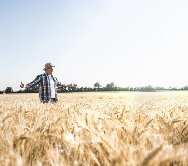 Happy senior farmer standing in wheat field - UUF11176