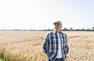 Relaxed senior farmer standing in front of wheat field - UUF11182
