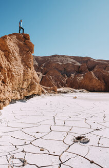 Chile, Atacama Desert, man standing on a red rock  looking at view - GEMF01742