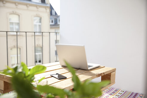 Laptop and smartphone on palette on balcony - MFRF00882