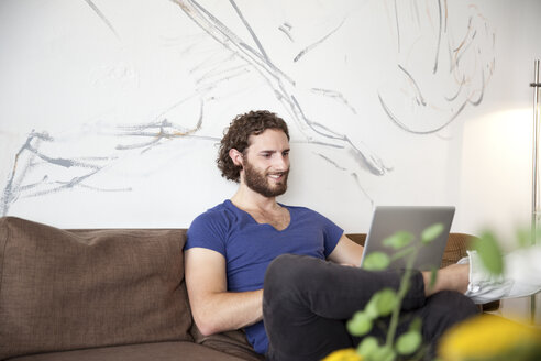 Smiling young man sitting on couch in a coffee shop using laptop - MFRF00903