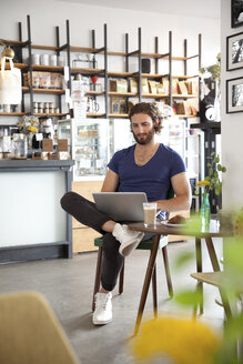 Portrait of young man sitting in a coffee shop using laptop - MFRF00909