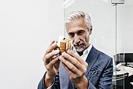 Mature businessman in office examining Rubik's Cube - KNSF02111