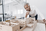 Mature businessman examining architectural model in office - KNSF02120