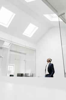 Happy mature businessman in office wearing headphones - KNSF02123