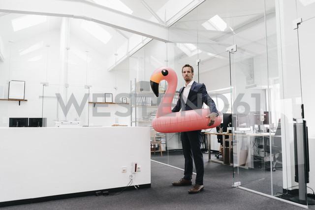 Businessman in office with inflatable flamingo - KNSF02138 - Kniel Synnatzschke/Westend61
