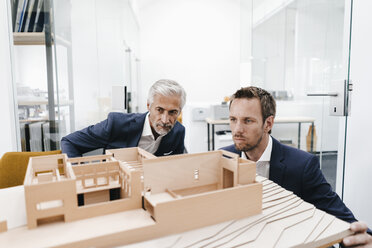 Two businessmen examining architectural model in office - KNSF02141