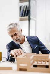 Mature businessman examining architectural model in office - KNSF02147