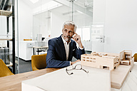 Mature businessman with architectural model in office - KNSF02150