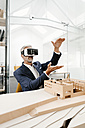 Mature businessman with architectural model in office wearing VR glasses - KNSF02156
