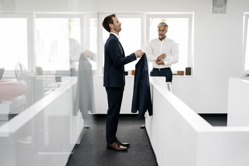 Employee in office holding jacket for his boss - KNSF02183