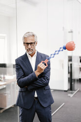 Mature businessman in office holding boxing toy - KNSF02189