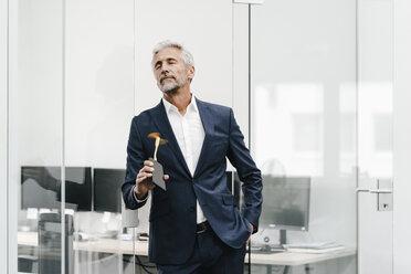 Mature businessman using fan in office - KNSF02204