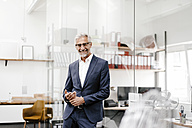 Portrait of smiling mature businessman in office - KNSF02207