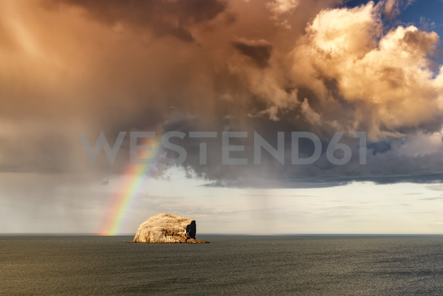 UK, Scotland, North Berwick, Firth of Forth, view of Bass Rock with rainbow and storm clouds - SMAF00776