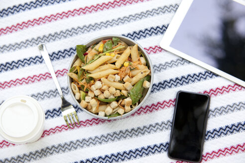 Cell phone, tablet, coffee to go and a bowl of noodle salad on blanket in a park - MFRF00916