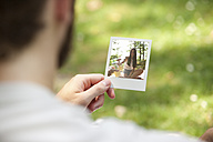 Man holding instant photo of his girlfriend, partial view - MFRF00928