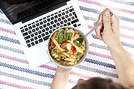 Man eating noodle salad on blanket in a park, partial view - MFRF00931