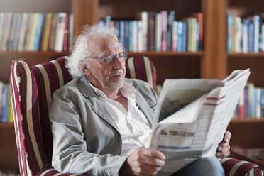 Senior man sitting in library, reading newpaper - ZEF14199
